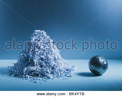 Metal globe next to pile of shredded paper - Stock Photo