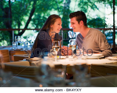 Couple holding hands at restaurant table - Stock Photo