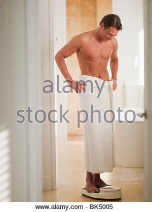 Man wrapped in a towel standing on bathroom scale with hands on hips - Stock Photo
