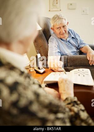 Elderly Couple in Retirement Home Working on Crossword Puzzle - Stock Photo