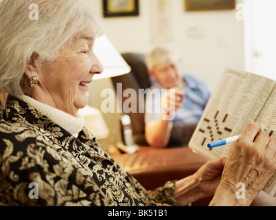 Elderly Couple in Retirement Home, Woman Working on Crossword Puzzle - Stock Photo