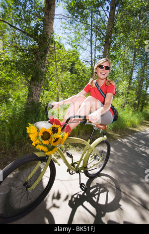 Woman Riding Bicycle, Near Steamboat Springs, Routt County, Colorado, USA - Stock Photo
