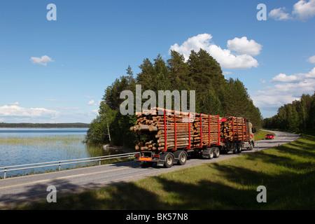 Truck transporting timber beside Lake Puruvesi, Punkaharju Nature Reserve, Saimaa Lake District, Savonia, Finland - Stock Photo