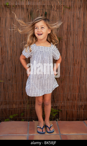 Wind blowing young girl in sundress - Stock Photo