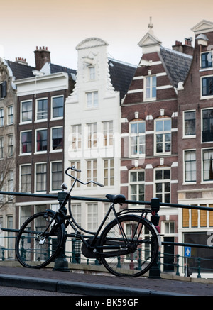 Bicycle parked on bridge above canal in central Amsterdam Netherlands - Stock Photo