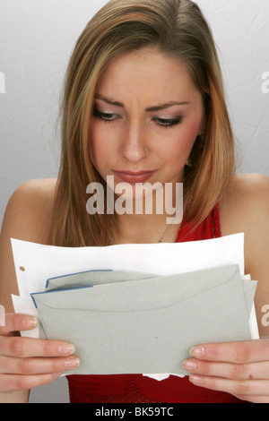 Financial trouble: Worried teenage girl holding financial statement and tax notes in hands needing debt relief - Stock Photo