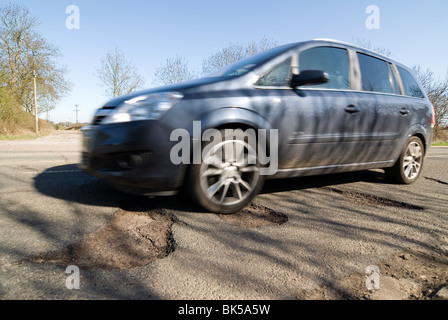 potholes in the middle of the road after a hard winter of snow. Who will pay for these pot holes to be repaired? - Stock Photo