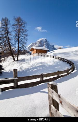 Winter snow covered mountain hut in front of Sassolungo mountain, Val Gardena, Dolomites, South Tirol, Italy - Stock Photo