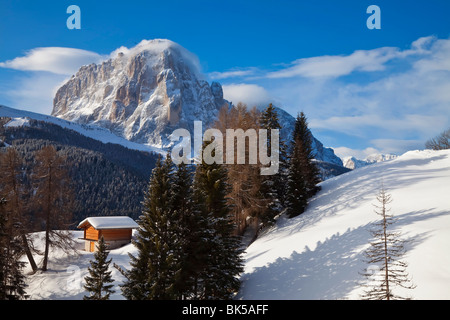 Winter snow covered mountain hut in front of Sassongher mountain, 2665m, Val Gardena, Dolomites, South Tirol, Italy - Stock Photo