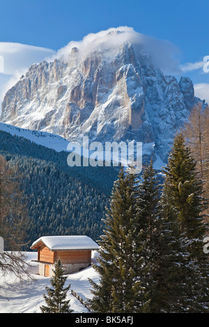 Winter snow covered mountain hut in front of Sassolungo mountain, 3181m, Val Gardena, Dolomites, South Tirol, Italy - Stock Photo