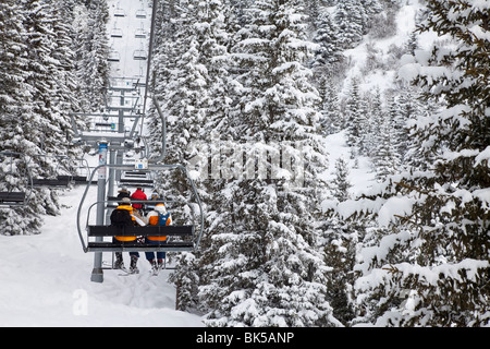 Skiers on a chairlift, Meribel ski resort in the Three Valleys (Les Trois Vallees), Savoie, French Alps, France, - Stock Photo
