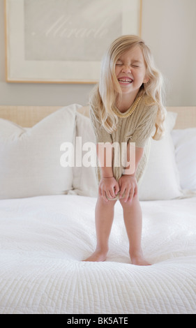 Girl with big smile standing on bed - Stock Photo
