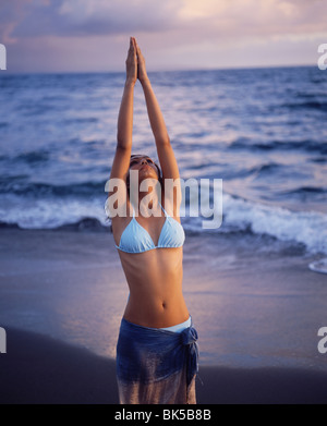 Indian girl doing the Salutation to the Sun yoga posture on the beach - Stock Photo