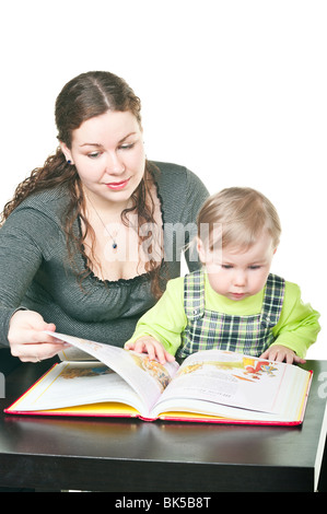 Little child and mother together read the book at a table. It is isolated on a white background - Stock Photo
