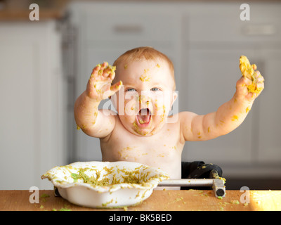 Happy baby playing in bowl of peas - Stock Photo