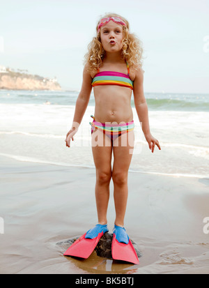 Girl in striped bikini and flippers at beach - Stock Photo