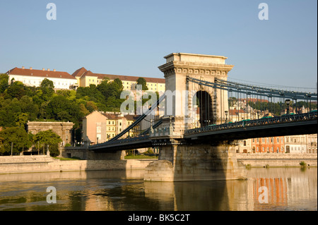 Early morning sailing under the Chain Bridge over the Danube River, Budapest, Hungary, Europe - Stock Photo