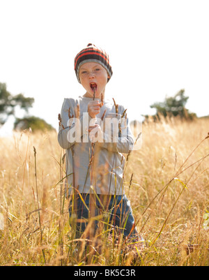 Boy singing in field - Stock Photo
