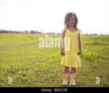 Young girl in yellow sundress and galoshes - Stock Photo