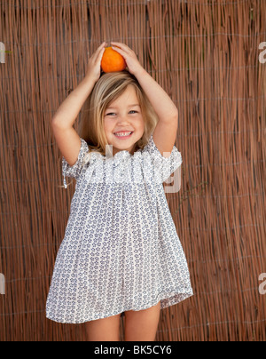 Young girl in sun dress holding an orange on her head - Stock Photo