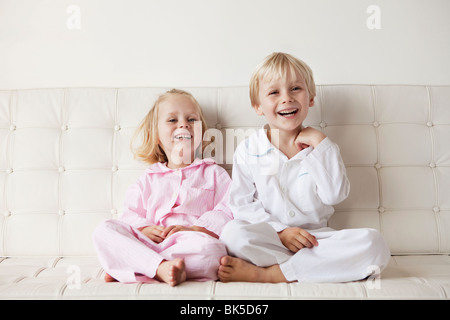 Young children in their pajamas sitting on the sofa