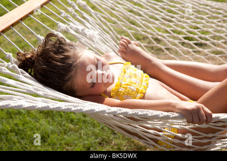 Little girl in yellow polka dot bikini on hammock - Stock Photo