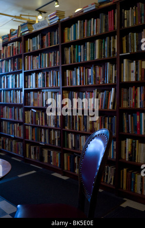 Tall bookshelves behind empty chair in café. - Stock Photo