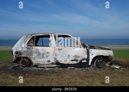 Stolen, abandoned and burnt out car on the foreshore at Granton, Edinburgh. - Stock Photo