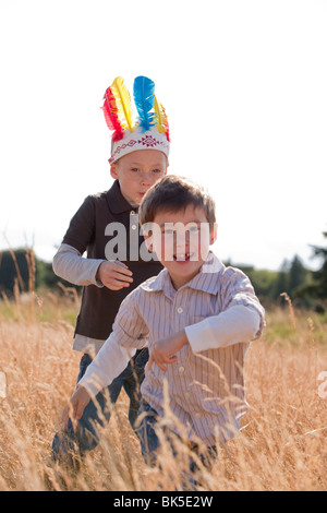 Young boys running in field - Stock Photo