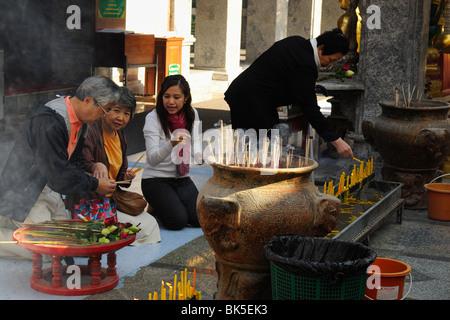 People burning incense sticks in Wat Phrathat Doi Suthep temple, Thailand, Southeast Asia - Stock Photo
