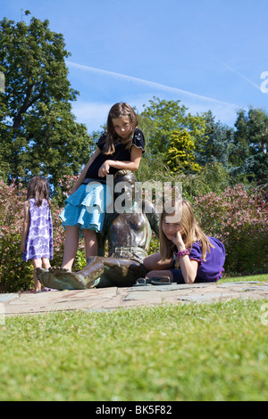 Children playing on statue, Golders Hill Park, bordering on Hampstead Heath, London, England, United Kingdom, Europe - Stock Photo