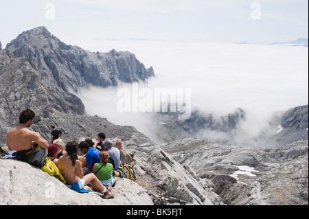 Hikers taking on Tesorero Peak, in Picos de Europa National Park, shared by the provinces of Asturias, Cantabria - Stock Photo