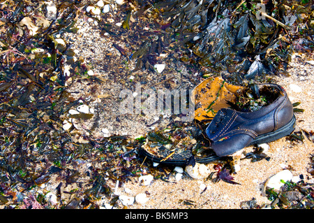 A single shoe on Broadstairs Beach, surrounded by seaweed, pebbles and shells. - Stock Photo