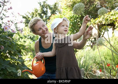 Mother and Daughter in Garden Watering Plants - Stock Photo