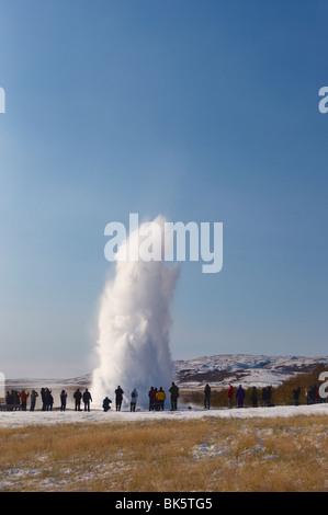 Tourists watching geyser erupting, Strokkur (the Churn), Geysir, Golden Circle, Iceland - Stock Photo