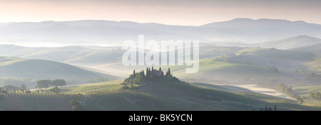 Misty dawn panoramic view across Val d'Orcia, UNESCO World Heritage Site, San Quirico d'Orcia, near Pienza, Tuscany, - Stock Photo