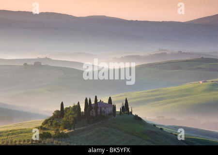 Misty dawn view across Val d'Orcia, UNESCO World Heritage Site, San Quirico d'Orcia, near Pienza, Tuscany, Italy - Stock Photo