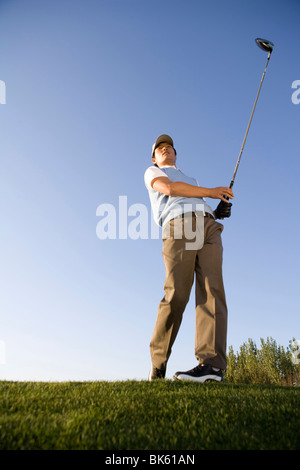 Golfer teeing off on the course - Stock Photo