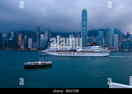 A Star Cruise tour sails through Victoria Harbor, in front of Hong Kong's Central District and the International - Stock Photo