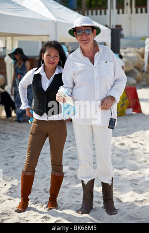 Young Asian woman and older Caucasian man. Married couple at a beach event. Thailand S. E. Asia - Stock Photo