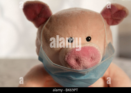 Toy pig with flu mask, head shot. - Stock Photo