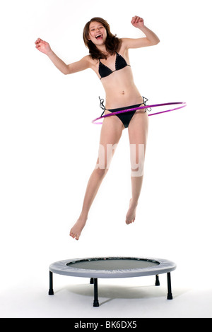 A laughing teenage girl in a bikini jumps on a trampoline with a hula hoop. - Stock Photo