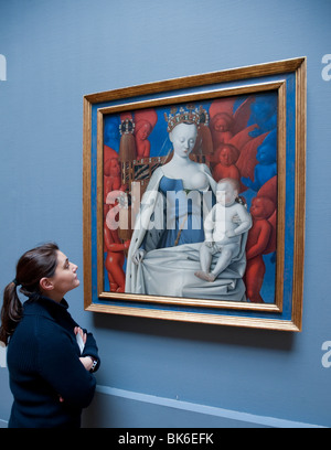 visitor looking at painting of Mary and Jesus surrounded by Seraphim and Cherubs by Jean Fouquet at Royal Museum - Stock Photo