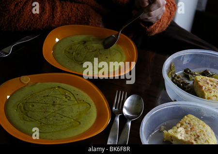 Pureed vegetables and Spanish omelet dishes on the table - Stock Photo