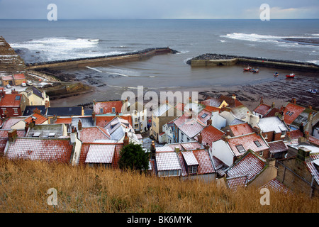 Winter weather & snow covered roofs. The snow covered tiled red rooftops of fishermen's houses in Staithes, North - Stock Photo