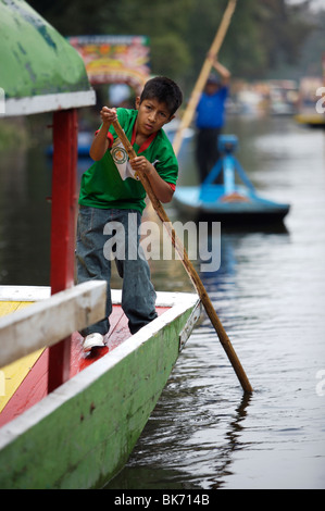 An boy uses a pole to navigate his boat through a canal in Xochimilco on the south side of Mexico City - Stock Photo