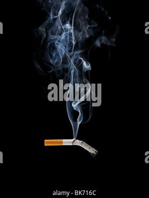 A Smoking cigarette on black background - Stock Photo