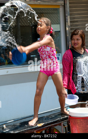 Young thai girls throws a bucket of water at Songkran festival in Koh Phangan Thailand - Stock Photo