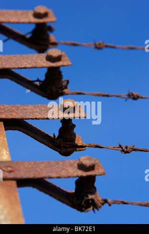 old rusty rusted end posts tensioners of a barbed wire security fence against a blue sky - Stock Photo