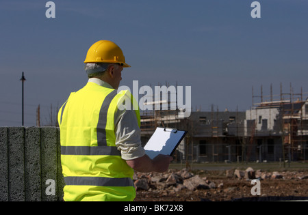 middle aged grey haired man wearing hard hat and hivis vest holding a clipboard building blocks on construction - Stock Photo